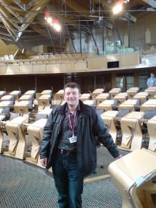 FOI Man standing in Scottish Parliament chamber