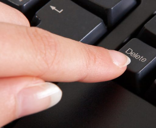 finger pressing delete key on a keyboard